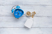 Blue clock with herb capsule on white wood background