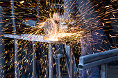 A worker is cutting iron with a circular metal saw and making sparks fly