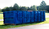 Large blue construction dumpster ready to be filled with debris from home renovations