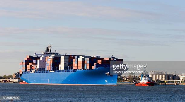Blue containership with containers being tugged in the Rotterdam harbour