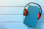 top view of audio book concept, blue cover book and headphones over wooden table