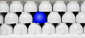 Blue cup amid white coffee cups