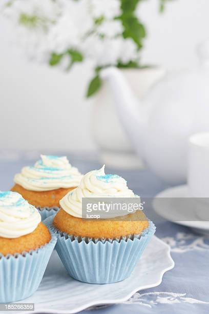 Blue cupcakes with vanilla icing with tea pot and cups background