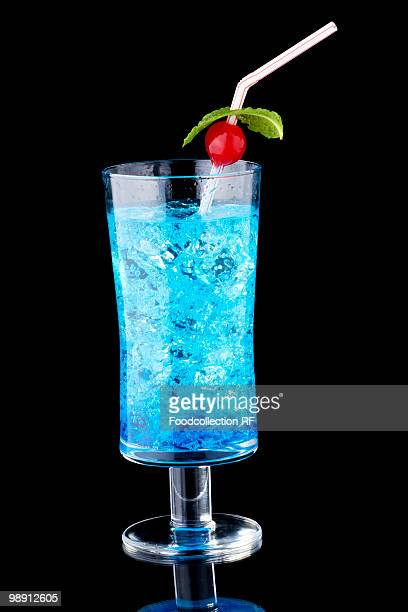 Blue curacao with crushed ice in glass on black background, close-up