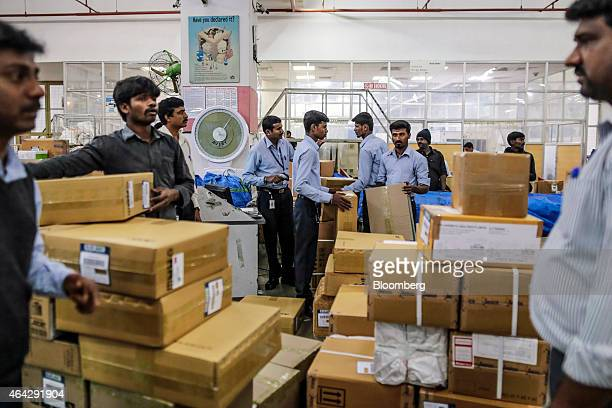 Blue Dart Express Ltd employees sort packages during the overnight sort inside the company's joint hub with DHL Express India Pvt in Cargo Terminal 3...