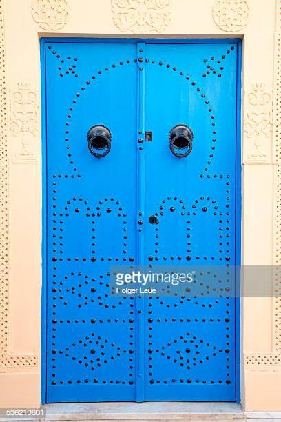 Blue doorway with lion doorknockers