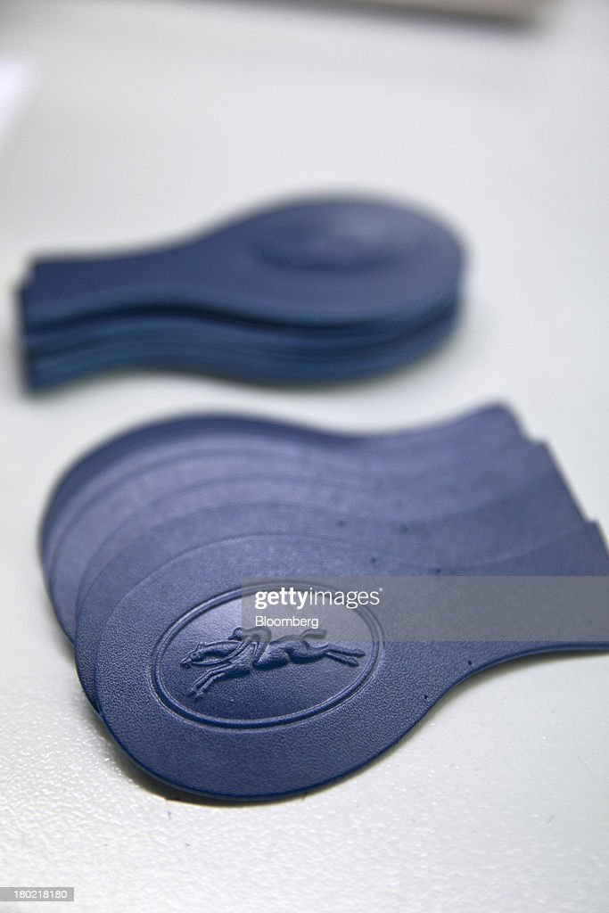 A blue embossed Longchamp logo is seen on a leather tab used during the production of Le Pliage Cuir bags at the Longchamp SAS workshop in Segre, France, on Monday, Sept. 9, 2013. Longchamp SAS, the French handbag maker, which is known for foldable Le Pliage nylon tote bags, expects sales in China to rise, Chief Executive Officer Jean Cassegrain said. Photographer: Balint Porneczi/Bloomberg via Getty Images