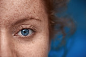 close up shot of woman with blue eye looking at camera, freckels on her skin, red hair.