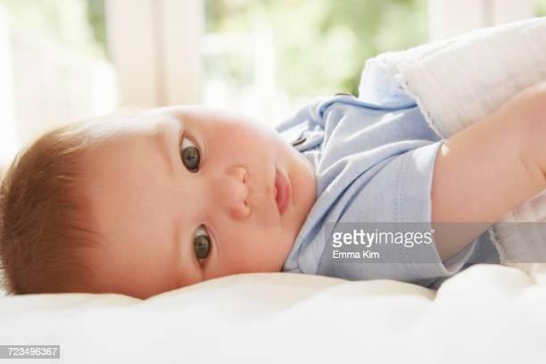 Blue eyed baby boy lying on back on bed
