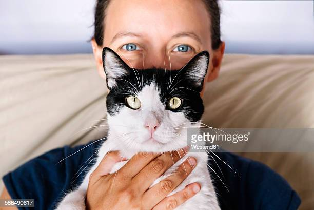Blue eyed woman holding a black and white cat