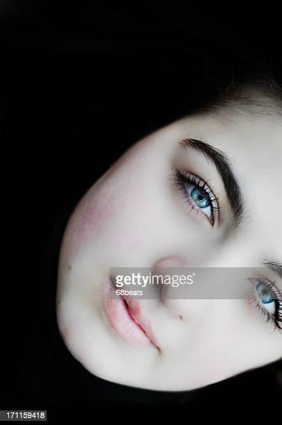 Blue eyed woman on dark background