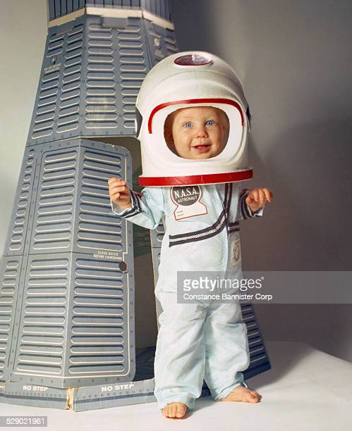 Blue eyes baby boy dressed as a crew member of the NASA Astronauts standing next to a cardboard Command Module called PowerMite II