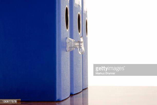 Blue file folders with valve standing on a desk, symbolic image for inflated bureaucracy
