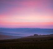 Surreal scenery of large blue fileds and a house silhouette contouring on dramatic colorful sky during dawn