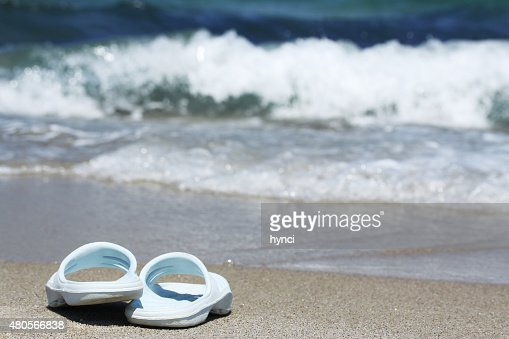Blue flip flops on sand beach in front of sea : Stock Photo