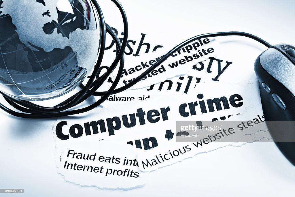 Blue glass globe paperweight, mouse on computer crime headlines : Stock Photo