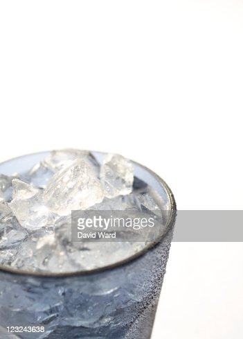 Blue glass of iced water on a white background.