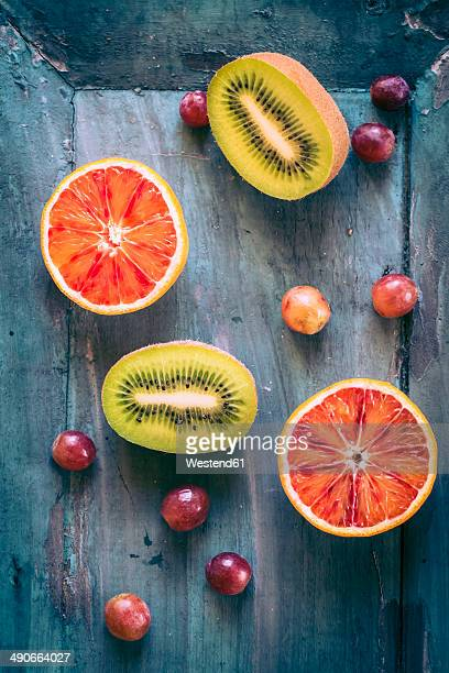 Blue grapes and two halves of blood orange and kiwi on blue wooden ground