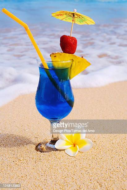 A Blue Hawaii tropical cocktail on the beach, wave washing on the sand.