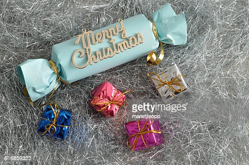 blue home made Christmas cracker with shiny wrapped small gift : Stock Photo