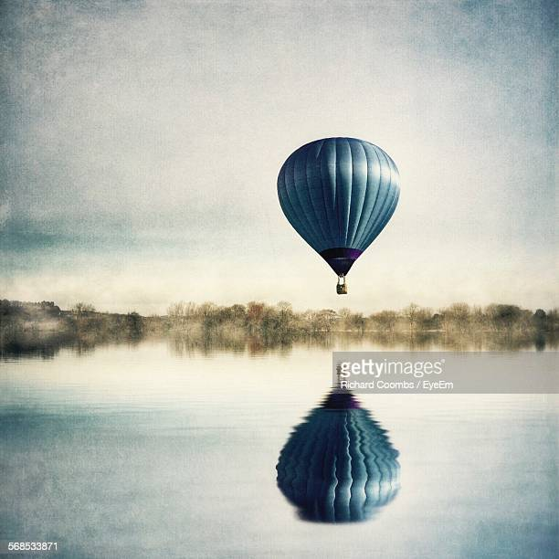 Blue Hot Air Balloon Flying Over Calm Lake