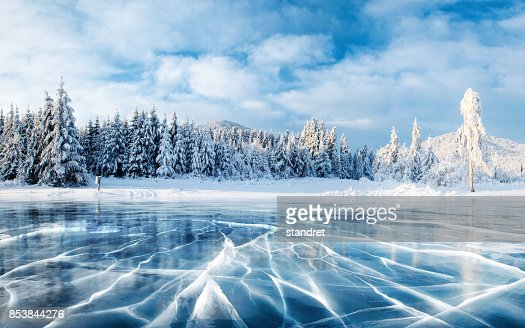 Blue ice and cracks on the surface of the ice. Frozen lake under a blue sky in the winter. The hills of pines. Winter. Carpathian, Ukraine, Europe. : Foto stock