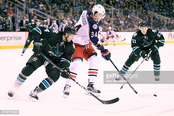 Blue Jackets right wing Josh Anderson cuts between Sharks defenseman Brenden Dillon and Tommy Wingels during the NHL game between the San Jose Sharks...