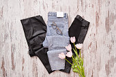 Blue jeans and black leather leggings, glasses, pink tulips. Fashionable concept. Top view