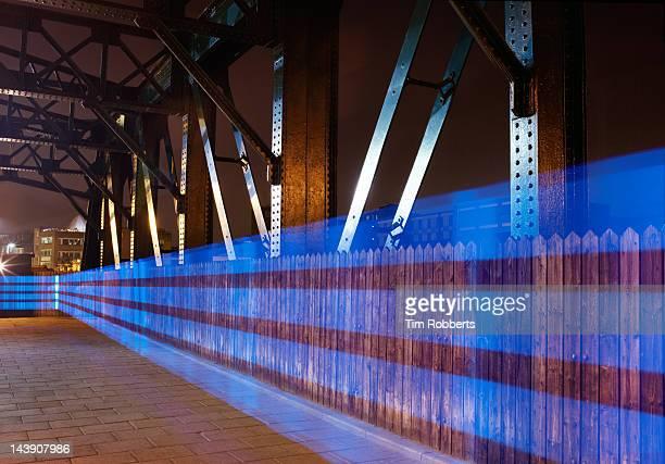 Blue light trail on bridge.