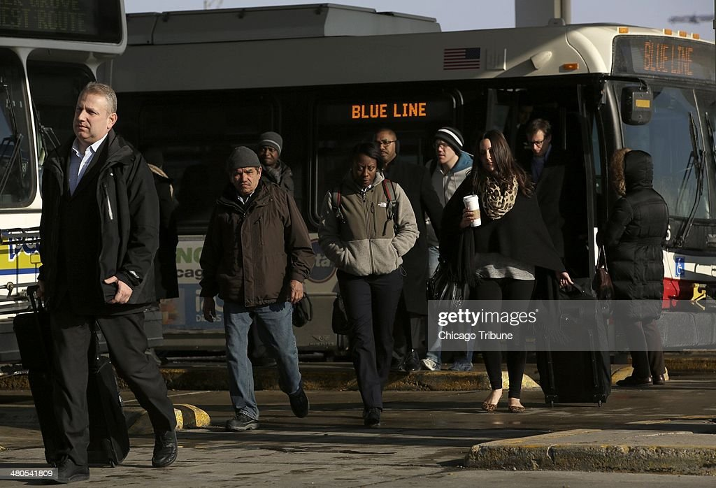 CTA Blue Line riders disembark shuttle buses from O'Hare International Airport at the Rosemont station, Tuesday, March 25, 2014, in Chicago. The O'Hare CTA station will be closed for several days as investigators work the scene of yesterday's train derailment.