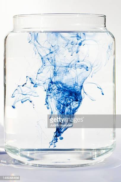 Blue liquid dissolving in water