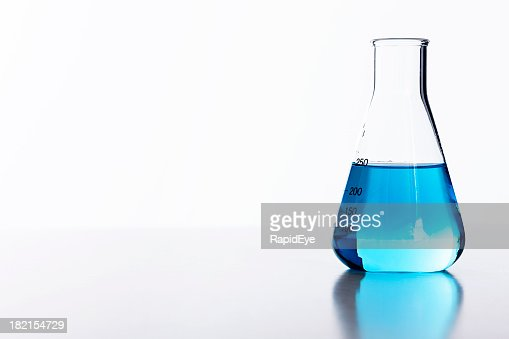 Blue liquid in half-filled laboratory flask against white background