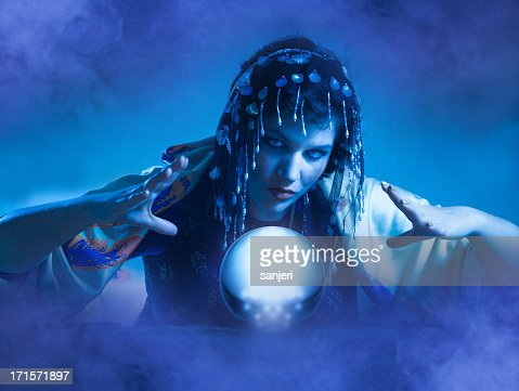 Blue lit fortune teller conjuring over a globe