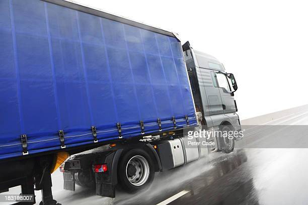 Blue lorry driving on wet road