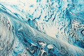Blue marbling texture form of wave. Creative background with abstract oil painted waves, handmade surface. Liquid paint.
