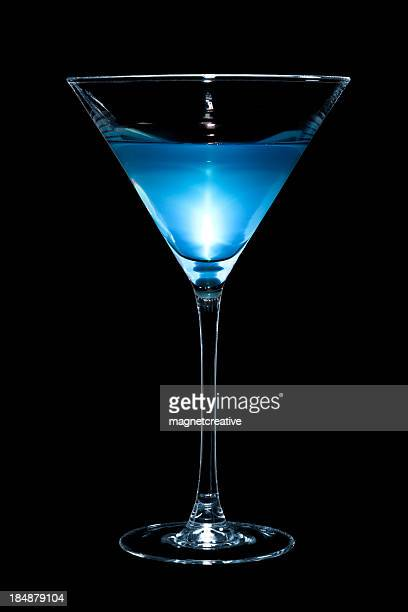 A blue martini cocktail surrounded in black