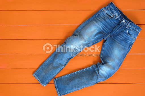 Blue mens jeans denim pants on orange background. Contrast saturated color. Fashion clothing concept. View from above : Stock Photo