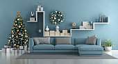 Blue modern living room with christmas tree,elegant sofa and white shelf with decor objects - 3d rendering