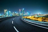 Blue neon light design highway overpass with modern city background . Night scene .
