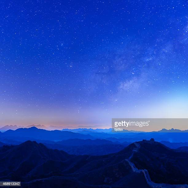 Blue, nighttime photo of the Great Wall under starry sky