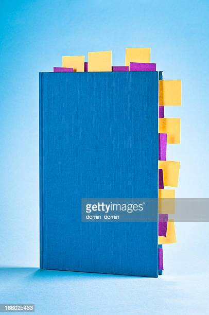 Blue notepad with yellow and purple sticky post-it notes