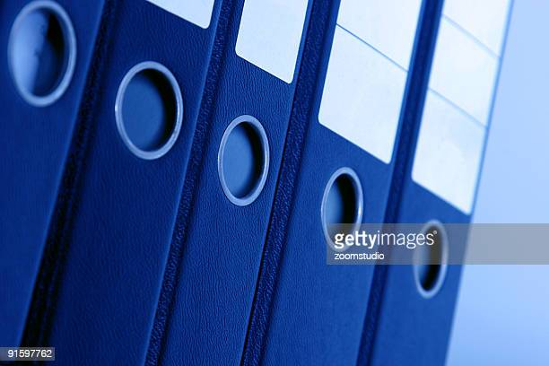 Blue office binders stacked in a row