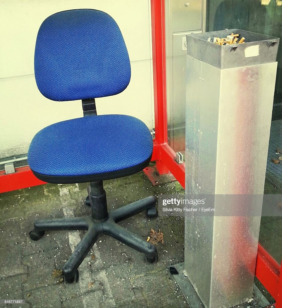Blue Office Chair Besides Dustbin Against Glass Wall