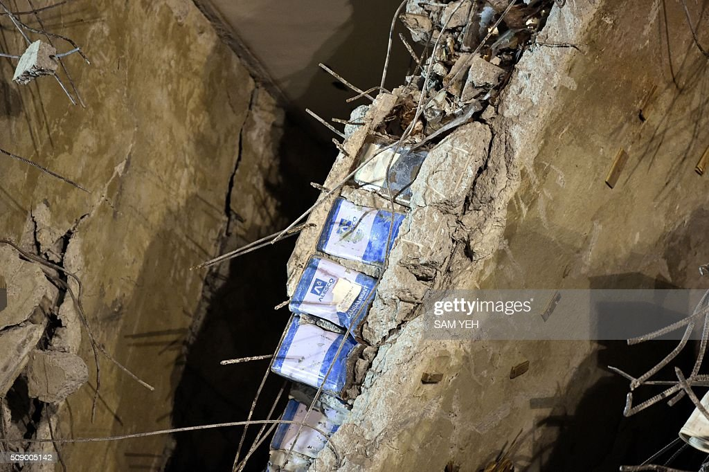 Blue paint cans, seen sandwiched in between a layer of concrete, is seen at the Wei-Kuan complex which collapsed in the 6.4 magnitude earthquake, in the southern Taiwanese city of Tainan on February 8, 2016. Four survivors on February 8 were pulled alive from the rubble of an apartment complex felled by an earthquake in Taiwan, as questions intensified over why the building collapsed. Images from the site showed metal cans and foam used inside the concrete framework of the building, raising questions over the safety of the construction. AFP PHOTO / Sam Yeh / AFP / SAM YEH