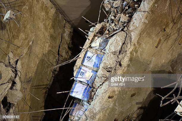 TOPSHOT Blue paint cans seen sandwiched in between a layer of concrete is seen at the WeiKuan complex which collapsed in the 64 magnitude earthquake...