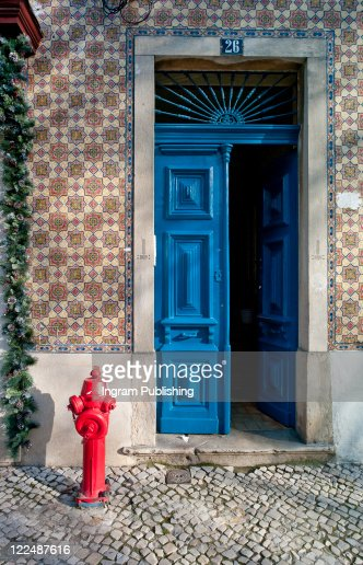 Blue painted front door and tiled building exterior with fire hydrant, Lisbon, Campo de Ourique : Stock Photo