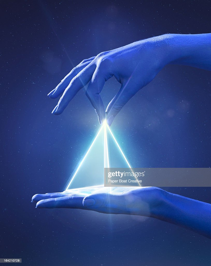 Blue painted hand pinching a glowing light prism : Stock Photo