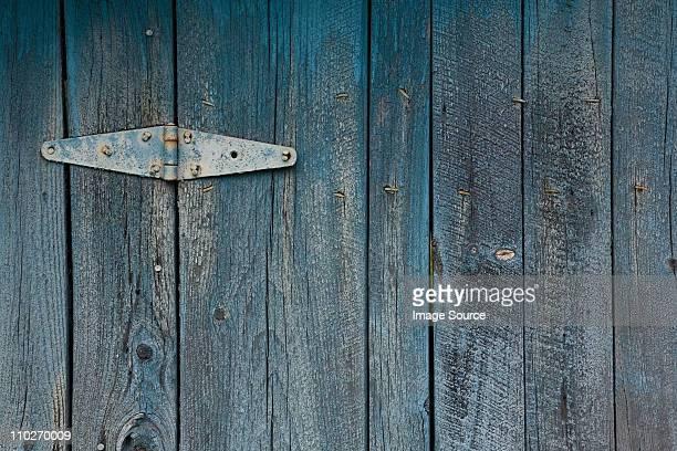 Blue painted wooden door with hinge