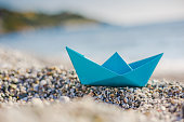 Blue paper boat on the pebble beach