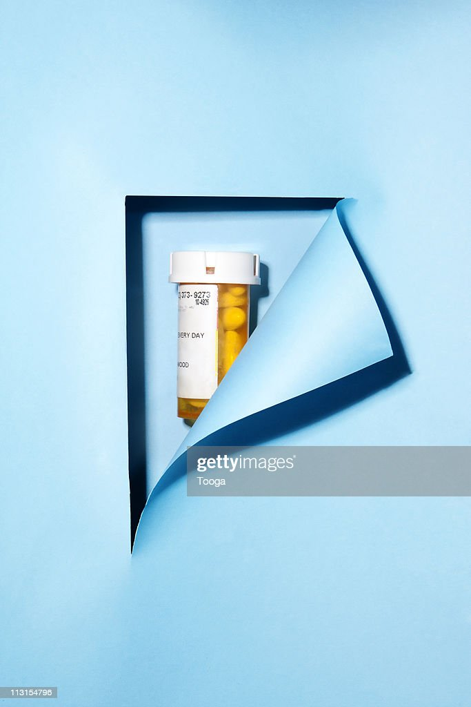 Blue paper  revealing prescrition bottle with pill